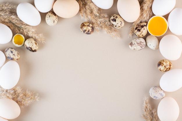 Ganze und zerbrochene frische rohe eier auf beigen tisch gelegt.