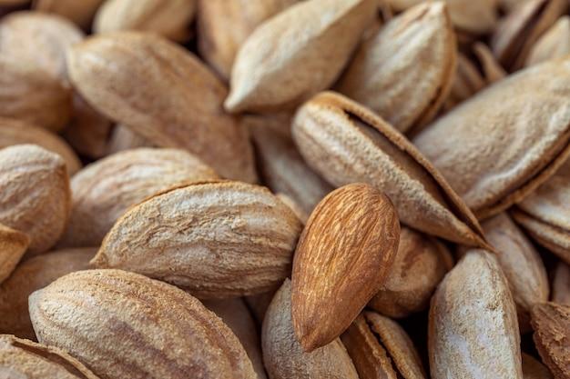 Ganze ungeschälte mandeln und eine geschälte nuss viele nüsse in nahaufnahme natürlicher hintergrund für ein gesundes ernährungskonzept