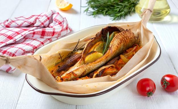 Ganzer fisch mit gemüse, kräutern und orange auf weißem holz gebacken