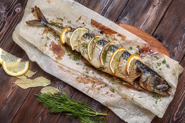 Ganzer gebackener makrelenfisch mit zitrone auf papier