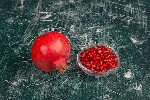 Ganzer granatapfel und samen auf marmortisch.
