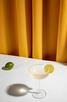 Ganzer kalk mit margaritacocktail im untertassenglas auf tabelle nahe dem vorhang