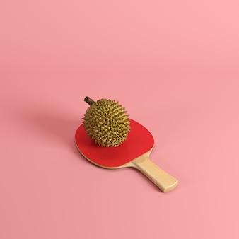 Ganzer reifer durian, könig von früchten, auf dem tischtennispaddel lokalisiert auf rosa hintergrund