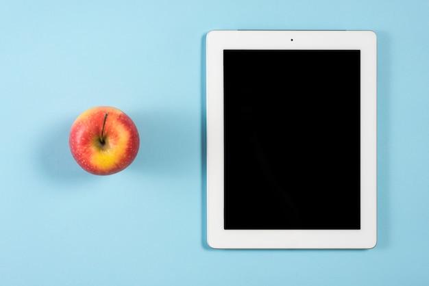 Ganzer roter apfel nahe der digitalen tablette mit leerem bildschirm auf blauem hintergrund