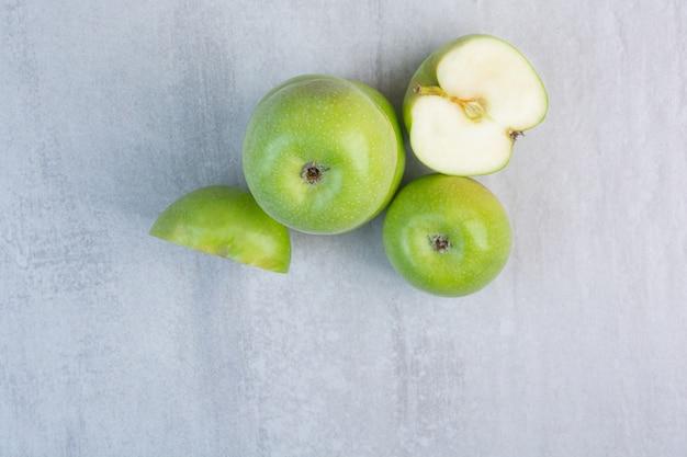 Ganzer und in scheiben geschnittener grüner leckerer apfel auf dem marmor.