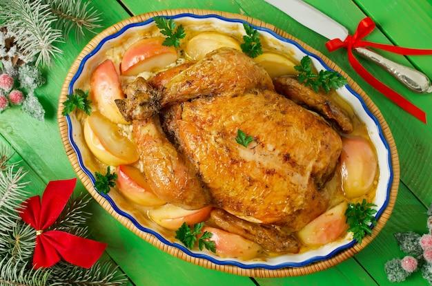 Ganzes brathähnchen gefüllt mit äpfeln, in einer cremigen sauce und apfelscheiben. weihnachtsessen