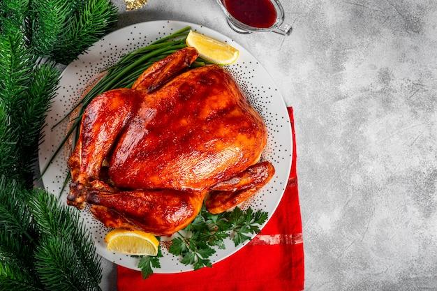 Ganzes gebackenes huhn in soße mit paprika auf einem teller und einer weihnachtlichen tischdekoration draufsicht