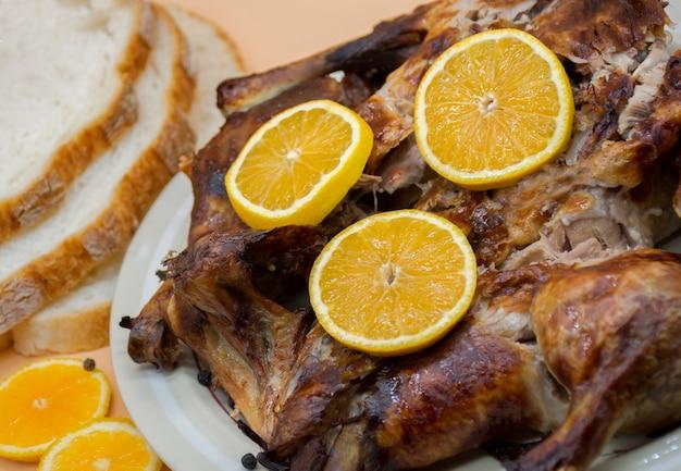 Ganzes gebratenes hähnchen oder ente auf weißem teller, dekoriert mit frischen orangen und brot