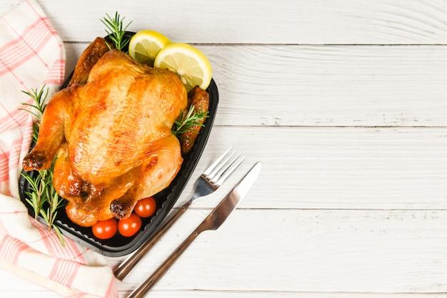 Ganzes gebratenes hühnerrosmarin und paprikazitrone - gebackenes huhn grillte köstliches lebensmittel des grills auf speisetische am feiertag feiern, draufsicht