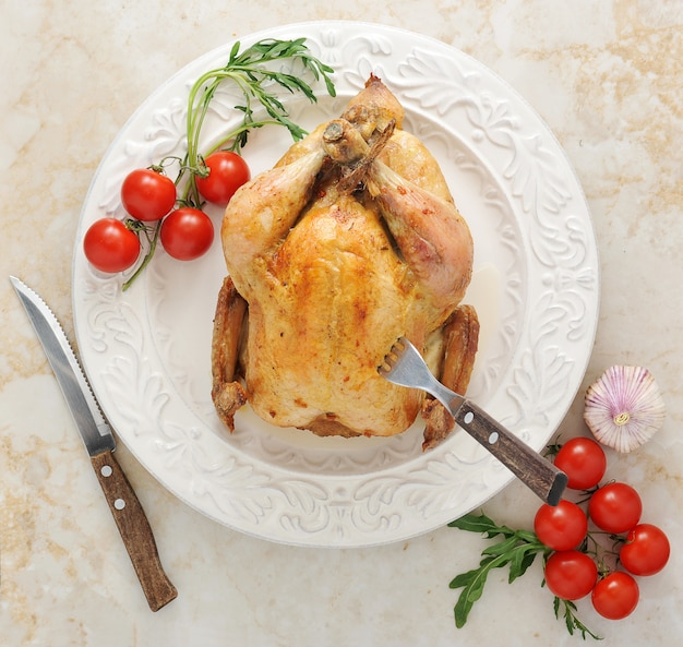 Ganzes gebratenes huhn auf einer platte mit tomaten und basilikum