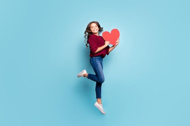 Ganzes körpergrößen-seitenprofilfoto des schulgrils, das herauf springt, das großes rotes herz hält, das zahnig im burgunderfarbenen pullover lächelt, der geschenkgeschenk lokalisierten blauen lebendigen farbhintergrund erhält