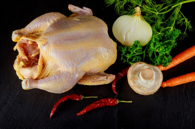 Ganzes rohes huhn mariniert und kochfertig mit zutaten zum kochen.