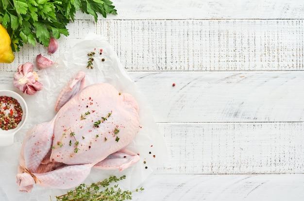 Ganzes rohes huhn mit zutaten für die herstellung von rosenpfeffer, zitrone, thymian, knoblauch, kirschtomate, sauerampfer und salz in der küche auf hellgrauem schiefer, stein oder betonhintergrund. ansicht von oben. platz kopieren