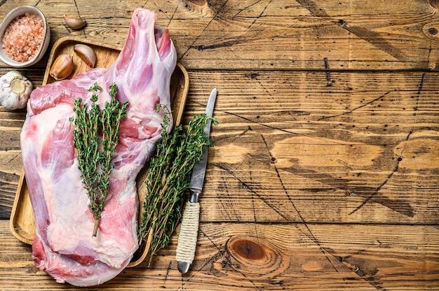 Ganzes rohes ziegenschulterbeinfleisch auf einem holztablett. hölzerner hintergrund. draufsicht. speicherplatz kopieren.