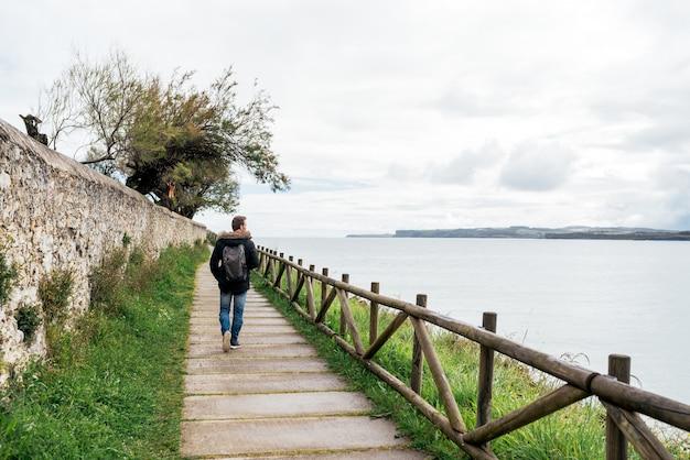 Ganzkörper anonymer junger männlicher reisender in freizeitkleidung, der auf steinweg mit holzzaun geht