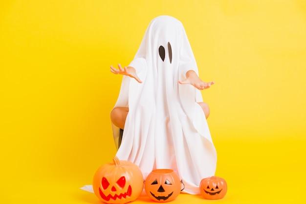 Ganzkörper eines kleinen niedlichen kindes mit weiß gekleidetem kostüm halloween-geist
