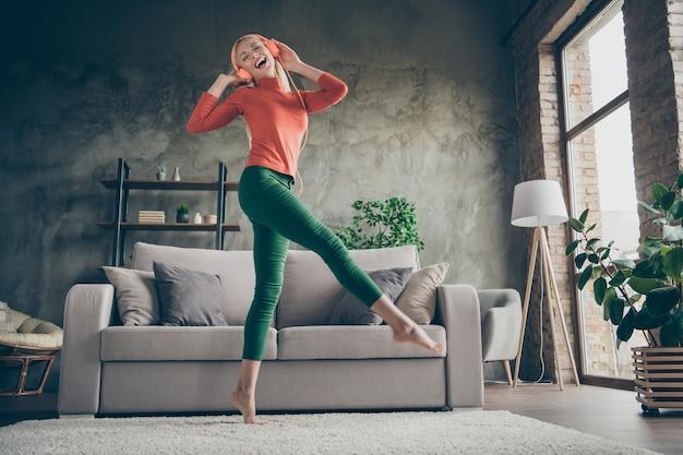 Ganzkörper-low-angle-view-foto von einer hübschen lustigen dame, die moderne moderne ohrhörer des telefonhörens hält, die in der nähe der couch lässiges outfit wohnzimmer drinnen tanzen