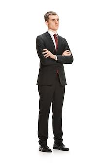 Ganzkörper- oder ganzkörperporträt des geschäftsmannes oder des diplomaten auf weißem studiohintergrund. ernsthafter junger mann im anzug, rote krawatte, die im amt steht.