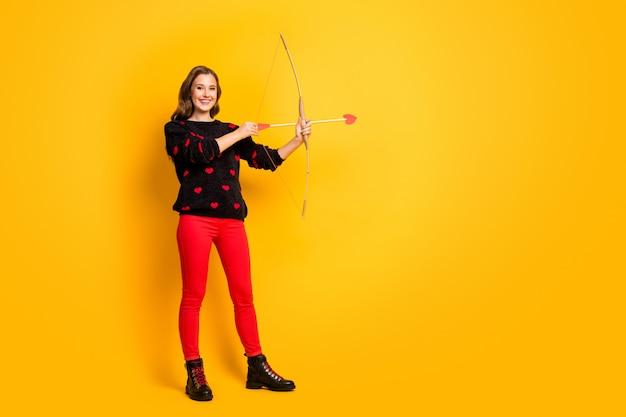 Ganzkörper-profilfoto der lustigen dame arbeit als amor halten bogen pfeil ziel gefühle liebespaar tragen herzen muster pullover rote hose schuhe