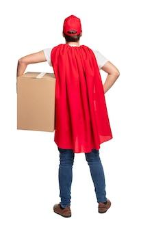 Ganzkörper-rückansicht des männlichen kuriers in der roten kappe und im umhang, die großen karton tragen, während paket liefern