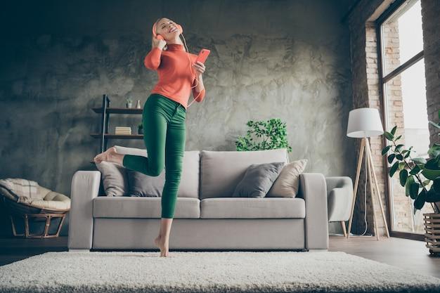 Ganzkörper tief unter winkelansicht foto der hübschen dame, die telefonhörlied moderne orange kopfhörer tanzt, die nahe couch lässiges outfit wohnzimmer drinnen tanzen