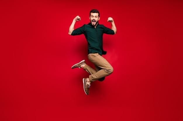 Ganzkörper von fröhlichen kerl springen zeigen seine kraft musclar hände trizeps gewinnen sportwettbewerb schrei fühlen sich verrückt ausdruck tragen grün braune hemd turnschuhe