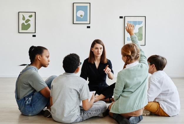 Ganzkörperansicht auf verschiedene gruppen von kindern, die während des unterrichts in der kunstgalerie mit lehrerin im kreis sitzen