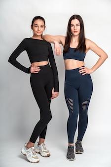 Ganzkörperansicht der asiatischen und kaukasischen mädchen in sportkleidung, die vor der kamera stehen und ihre perfekten körper zeigen. stock foto