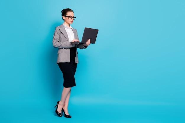 Ganzkörperansicht der netten fokussierten dame geek it-experte übergibt laptop, der aus der ferne isoliert über hellblauem hintergrund arbeitet