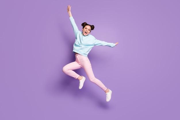 Ganzkörperansicht der schönen, attraktiven, schönen, schlanken, ekstatischen, fröhlichen mädchen, die springen und spaß beim täuschen haben, einzeln auf violett-violetter, heller, lebendiger, leuchtender farbhintergrund