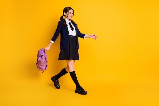 Ganzkörperansicht des hübschen fröhlichen schulmädchen-nerds, der zurück zur schule geht, tragetasche