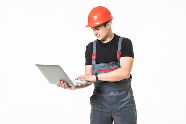Ganzkörperansicht eines bauunternehmers, der an seinem laptop auf weißem hintergrund arbeitet