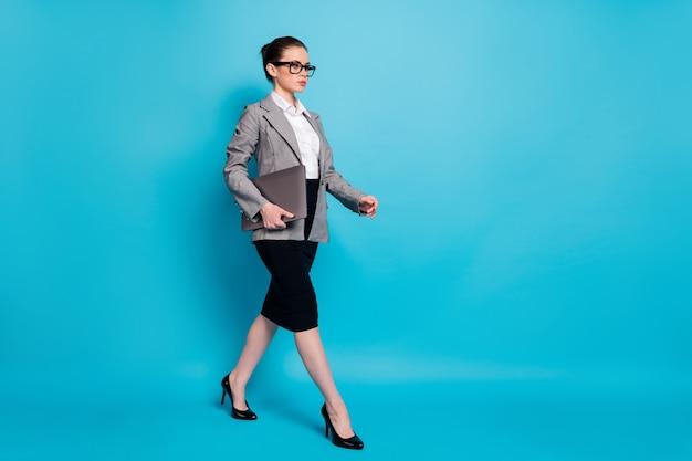 Ganzkörperansicht in voller länge von schönem inhalt, intelligenter, klassischer damenspezialist, der einen laptop trägt, der isoliert über hellblauem hintergrund läuft