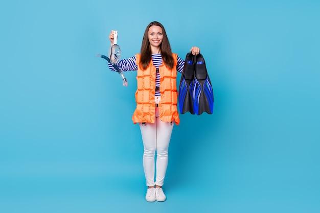 Ganzkörperansicht von ihr, sie attraktives fröhliches fröhliches mädchen, das eine orangefarbene weste trägt, die in den händen hält tauchausrüstungszubehör isoliert heller, lebendiger, leuchtender blauer farbhintergrund