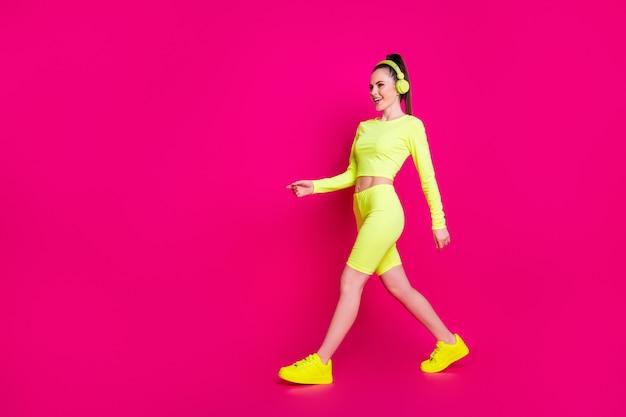 Ganzkörperansicht von ihr, sie hübsches, attraktives, charmantes, schlankes, sportliches, fröhliches mädchen, das pop-rock-melodie-musik hört, die isoliert heller, lebendiger glanz, lebendiger rosa fuchsia-farbhintergrund