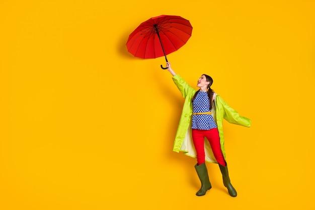 Ganzkörperansicht von ihr, sie schönes attraktives modisches, trendiges fröhliches fröhliches mädchen mit grünem regenmantel, der mit hurrikan kämpft, isoliert hell leuchtend gelber farbhintergrund