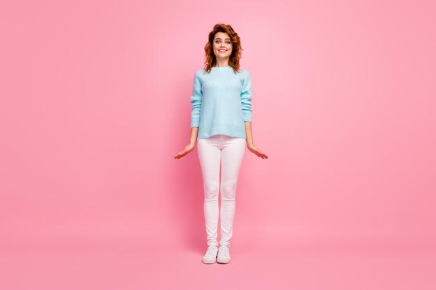 Ganzkörperansicht von ihr, sie sieht gut aus, attraktiv, hübsch, süß, feminin, fröhlich, fröhlich, gewelltes mädchen, das einzeln auf rosafarbenem pastellfarbenhintergrund posiert