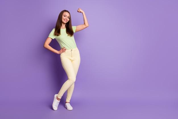 Ganzkörperansicht von ihr, sie sieht gut aus, attraktiv, kraftvoll, fröhlich, starkes mädchen, das die motivation des bizeps-fitnessstudios demonstriert, isoliert über hell leuchtendem, leuchtendem, lila-violettem farbhintergrund
