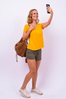 Ganzkörperaufnahme der glücklichen blonden touristenfrau mit rucksack, der selfie nimmt