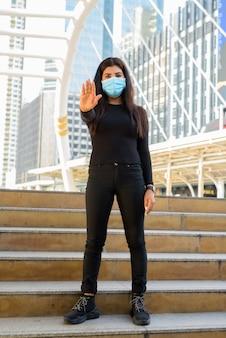 Ganzkörperaufnahme der jungen indischen frau mit maske, die stoppgeste durch die treppe in der stadt zeigt