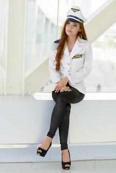 Ganzkörperaufnahme der jungen schönen asiatischen marinefrau, die drinnen am fenster sitzt
