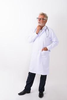 Ganzkörperaufnahme des hübschen älteren bärtigen mannarztes stehend und denkend, während auf weiß schauend