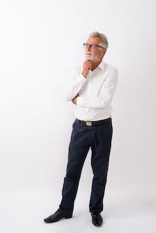 Ganzkörperaufnahme des hübschen älteren bärtigen mannes, der steht, während er auf weiß denkt und schaut