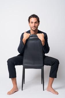 Ganzkörperaufnahme des hübschen hispanischen geschäftsmannes, der weg schaut, während er auf stuhl sitzt