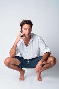 Ganzkörperaufnahme des hübschen hispanischen mannes, der hockt, während er am telefon spricht