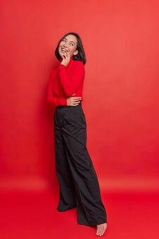 Ganzkörperaufnahme einer glücklichen, verträumten, brünetten jungen asiatin hat einen positiven ausdruck, trägt eine schwarze, lockere hose mit rollkragen, steht gegen eine leuchtend rote wand und denkt an etwas sehr angenehmes