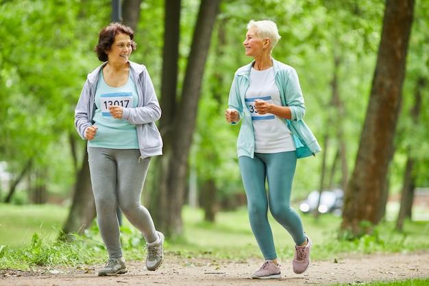 Ganzkörperaufnahme von zwei aktiven älteren frauen, die marathonlauf im stadtpark laufen, die miteinander sprechen