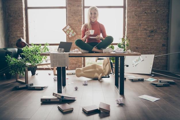 Ganzkörperfoto der glücklichen händlerfrau sitzen auf dem tisch gekreuzte beine fühlen sich sorglos sorglos ruhe entspannen halten weiße kaffeetasse in unordentlich büro loft halten