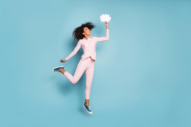 Ganzkörperfoto der hübschen dunklen hautdame, die hoch hält, hält papierwolkengeist in der hand kreative art der kommunikation tragen rosa hemdhose isoliert blauen farbhintergrund