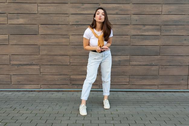 Ganzkörperfoto der hübschen jungen, glücklichen frau, die freizeitkleidung trägt und zuhört